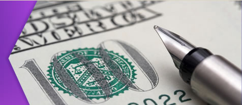 Caligraphy pen laying on hundred-dollar bill